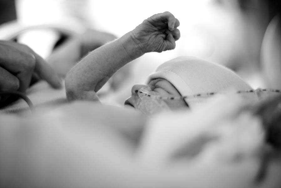 A baby in an incubator with a nasal gastric feeding tube, holding his arm in the air with a clasped fist.