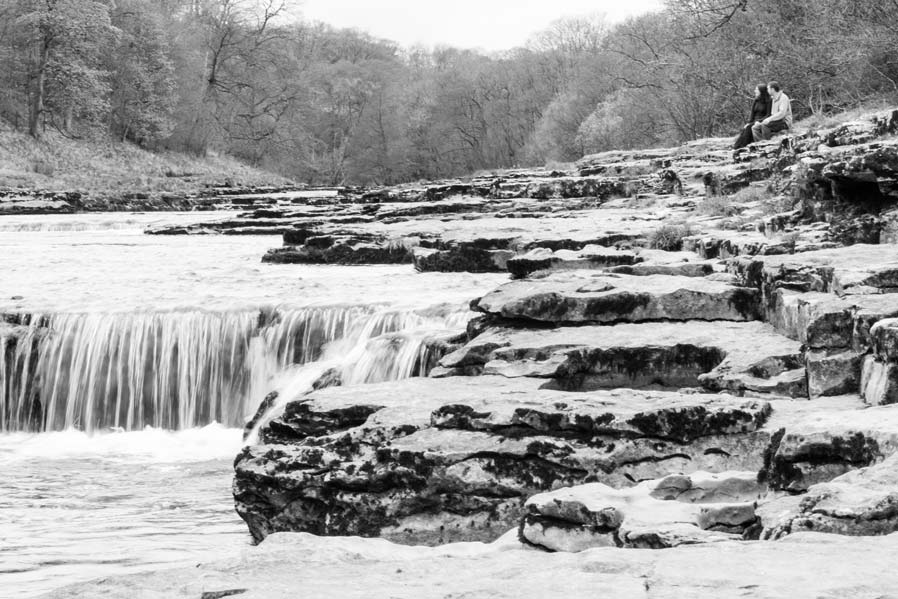 An image in Black and White f a couple taken at Aysgarth Falls on their Pre-Wedding photo session, this is carried out a few ekes before the wedding.