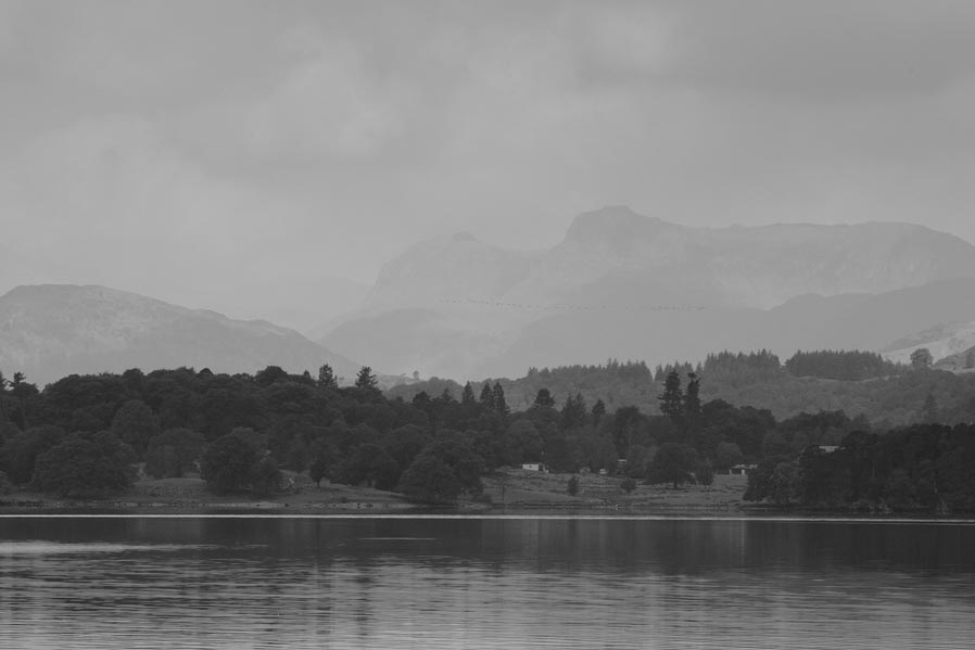 A black and white images of the Langdales taken from the Low Wood Bay.
