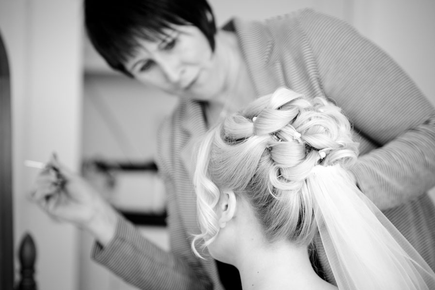 Photograph in Black and White of a make-up artist applying wedding make-up.