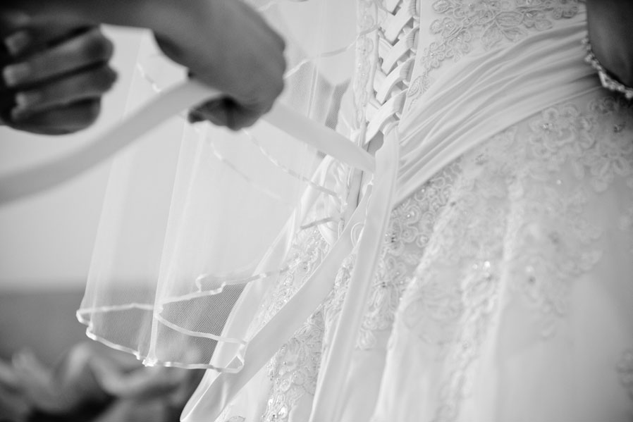 Wedding gown being fastened by mother of the bride, photograph in black and white.