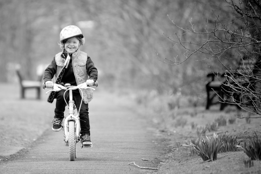 A young girl takes to her bicycle as she learns to ride without stabilisers, precious moments.