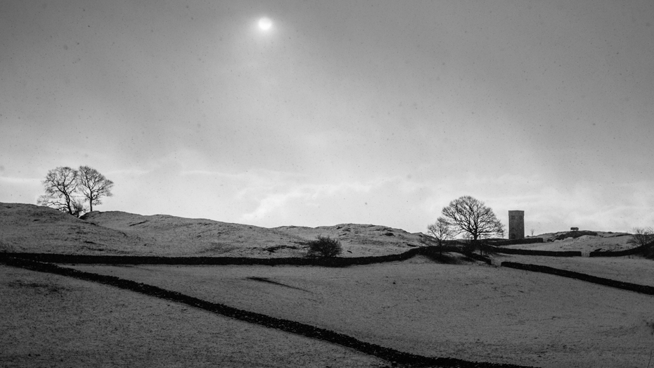 Black and white image of snow falling before a winter wedding at Crook Church in Cumbria by Ian Wood Photography who is a wedding photographer in Kendal.